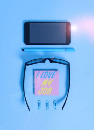 Word writing text I Love My Job. Business photo showcasing Enjoying the daily tasked assigned Contented on the occupation Dark eyeglasses colored sticky note smartphone pen clips pastel background Stock fotó