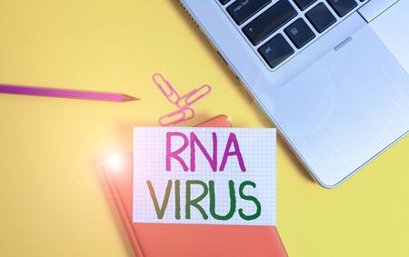 Writing note showing Rna Virus. Business concept for a virus genetic information is stored in the form of RNA Laptop clips pencil paper sheet hard cover notebook colored background