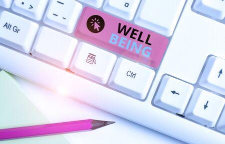 Koncepcyjne pismo ręczne pokazujące dobre samopoczucie. Pojęcie oznacza Dobry lub zadowalający stan egzystencji, w tym zdrowie Biała klawiatura komputera z papierem nutowym nad białym tłem