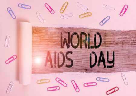 Conceptual hand writing showing World Aids Day. Concept meaning 1st December dedicated to raising awareness of the AIDS Paper clip and torn cardboard on wood classic table backdrop