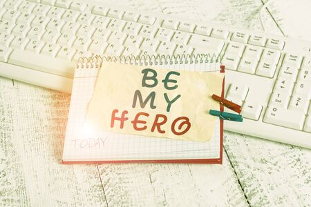 Conceptual hand writing showing Be My Hero. Concept meaning Request by someone to get some efforts of heroic actions for him notebook reminder clothespin with pinned sheet light wooden Imagens