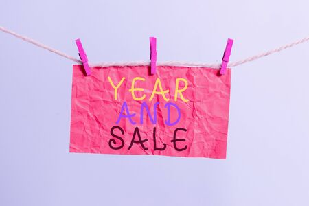 Handwriting text writing Year And Sale. Conceptual photo Annual Discounts Holiday Season clearance Traditional Clothesline clothespin rectangle shaped paper reminder white wood desk