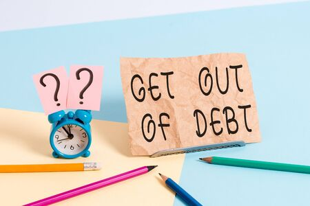 Conceptual hand writing showing Get Out Of Debt. Concept meaning No prospect of being paid any more and free from debt Mini size alarm clock beside stationary on pastel backdrop