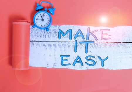 Handwriting text writing Make It Easy. Conceptual photo Smart approach Effortless Free from worries or difficulties Alarm clock and torn cardboard placed above a wooden classic table backdrop