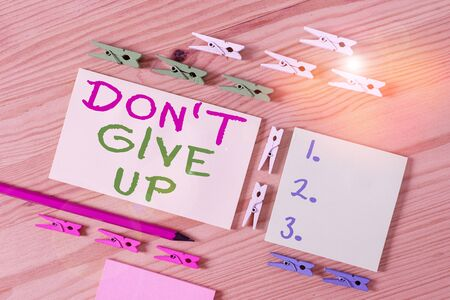 Text sign showing Don T Give Up. Business photo showcasing Determined Persevering Continue to Believe in Yourself Colored clothespin papers empty reminder wooden floor background office Stock fotó