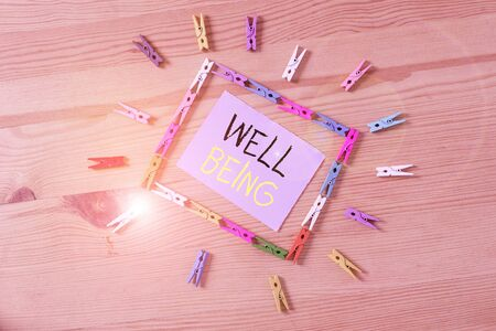 Word writing text Well Being. Business photo showcasing A good or satisfactory condition of existence including health Colored clothespin papers empty reminder wooden floor background office