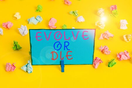 Text sign showing Evolve Or Die. Business photo showcasing Necessity of change grow adapt to continue living Survival Colored crumpled papers empty reminder white floor background clothespin Zdjęcie Seryjne - 134162644