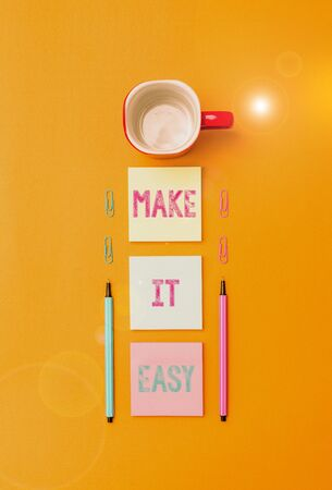 Text sign showing Make It Easy. Business photo text Smart approach Effortless Free from worries or difficulties Coffee cup blank colored sticky note two ballpoints clips yolk background