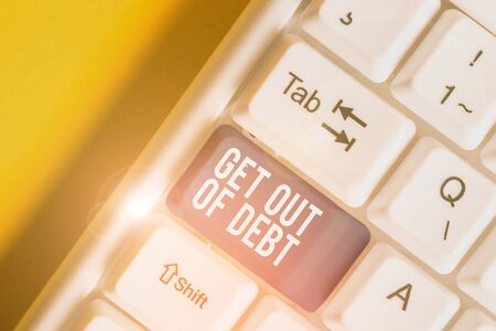 Conceptual hand writing showing Get Out Of Debt. Concept meaning No prospect of being paid any more and free from debt White pc keyboard with note paper above the white background 스톡 콘텐츠