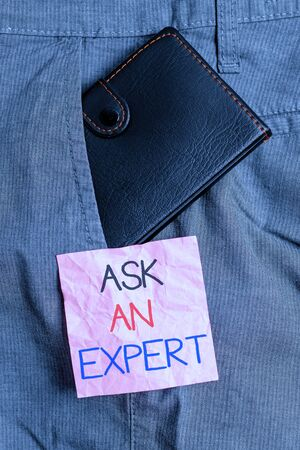 Text sign showing Ask An Expert. Business photo text Superior Reliable Ace Virtuoso Curapp storeity Authority Geek Small little wallet inside man trousers front pocket near notation paper Zdjęcie Seryjne - 134162263