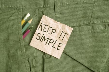 Text sign showing Keep It Simple. Business photo text Remain in the simple place or position not complicated Writing equipment and pink note paper inside pocket of man work trousers