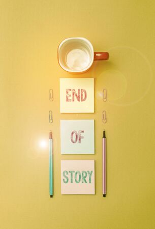 Text sign showing End Of Story. Business photo text Emphasize that nothing to add Literature writing Journalism Coffee cup blank colored sticky note two ballpoints clips yolk background