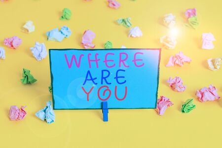 Text sign showing Where Are You. Business photo showcasing Give us your location address direction point of reference Colored crumpled papers empty reminder white floor background clothespin