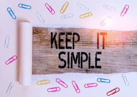Conceptual hand writing showing Keep It Simple. Concept meaning Remain in the simple place or position not complicated Paper clip and torn cardboard on wood classic table backdrop Stock Photo