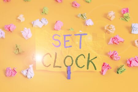 Handwriting text writing Set Clock. Conceptual photo put it to the right time or change the clock time to a later time Colored crumpled papers empty reminder white floor background clothespin Zdjęcie Seryjne - 134164053