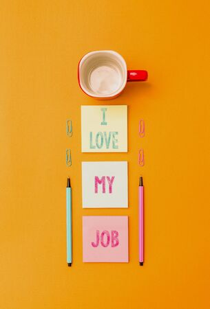 Text sign showing I Love My Job. Business photo text Enjoying the daily tasked assigned Contented on the occupation Coffee cup blank colored sticky note two ballpoints clips yolk background Stock fotó