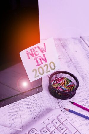 Writing note showing New In 2020. Business concept for list of fresh things got introduced this year or the next Note paper taped to black computer screen near keyboard and stationary