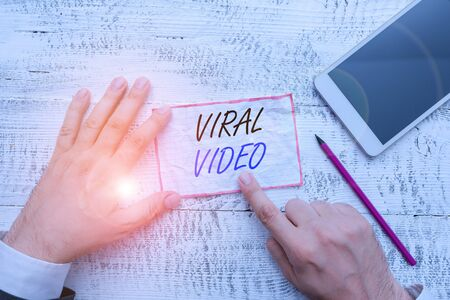 Writing note showing Viral Video. Business concept for the video that becomes popular through internet sharing Hand hold note paper near writing equipment and smartphone Stock Photo