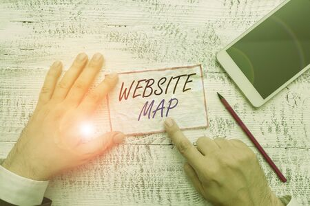 Writing note showing Website Map. Business concept for designed to help both users and search engines navigate the site Hand hold note paper near writing equipment and smartphone