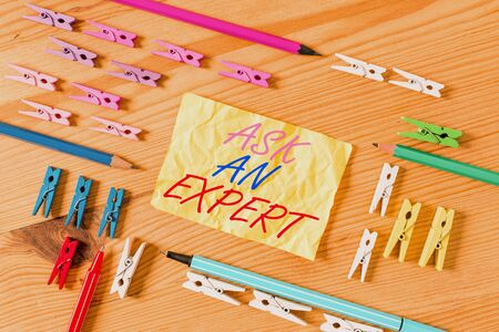 Text sign showing Ask An Expert. Business photo showcasing Superior Reliable Ace Virtuoso Curapp storeity Authority Geek Colored clothespin papers empty reminder wooden floor background office Zdjęcie Seryjne