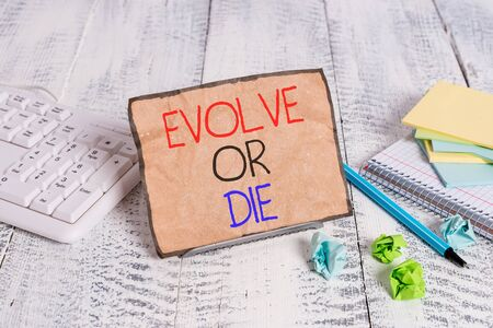 Conceptual hand writing showing Evolve Or Die. Concept meaning Necessity of change grow adapt to continue living Survival Notepaper on wire in between computer keyboard and sheets