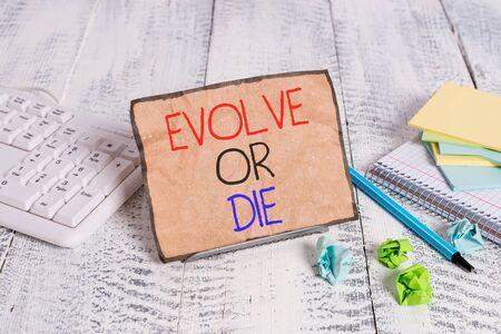 La main conceptuel montrant évoluer ou mourir. Sens Concept nécessité de changement grandir s'adapter pour continuer à vivre Survival Notepaper sur le fil entre le clavier de l'ordinateur et les feuilles