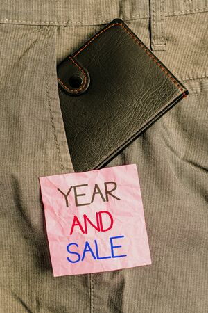Text sign showing Year And Sale. Business photo text Annual Discounts Holiday Season clearance Traditional Small little wallet inside man trousers front pocket near notation paper