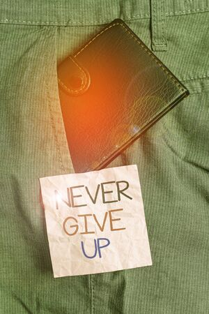 Text sign showing Never Give Up. Business photo text Keep trying until you succeed follow your dreams goals Small little wallet inside man trousers front pocket near notation paper Stockfoto
