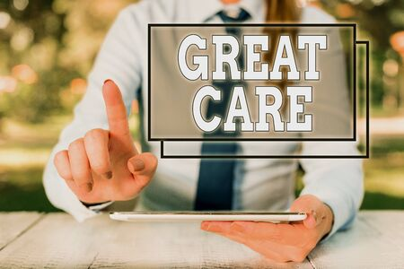 Text sign showing Great Care. Business photo text to treat someone with great or excessive care or kindness Female business person sitting by table and holding mobile phone Zdjęcie Seryjne - 134166273