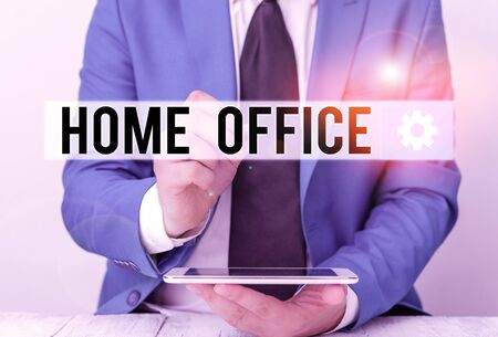 Writing note showing Home Office. Business concept for space designated in a demonstrating s is residence for official business Businessman pointing with pen in empty copy space