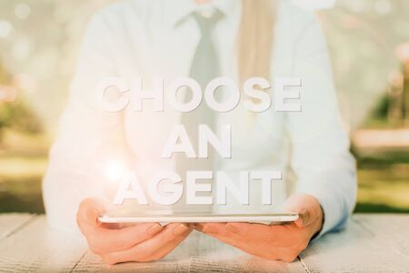 Handwriting text writing Choose An Agent. Conceptual photo Choose someone who chooses decisions on behalf of you Female business person sitting by table and holding mobile phone
