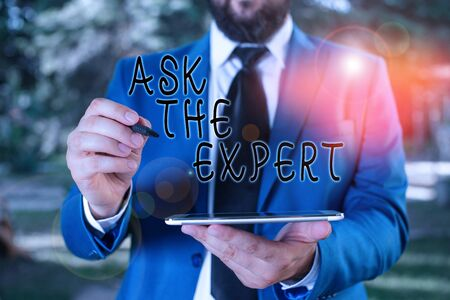 Writing note showing Ask The Expert. Business concept for Looking for professional advice Request Help Support Businessman in blue suite stands with mobile phone in hands