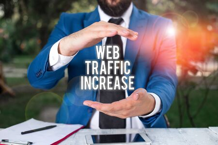 Conceptual hand writing showing Web Traffic Increase. Concept meaning Expand Visitors to a Website a number of Visits Man in front of table. Mobile phone and notes on the table