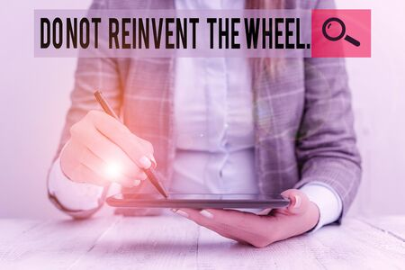 Writing note showing Do Not Reinvent The Wheel. Business concept for stop duplicating a basic method previously done Business woman sitting with mobile phone and pen in the hand