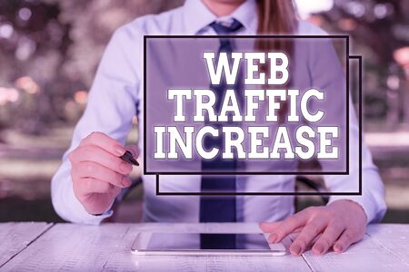 Text sign showing Web Traffic Increase. Business photo showcasing Expand Visitors to a Website a number of Visits Female business person sitting by table and holding mobile phone Stockfoto