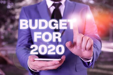 Conceptual hand writing showing Budget For 2020. Concept meaning An written estimates of income and expenditure for 2020 Businessman with pointing finger in front of him