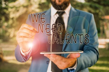 Writing note showing We Need Talents. Business concept for seeking for creative recruiters to join company or team Businessman in blue suite stands with mobile phone in hands