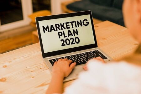 Text sign showing Marketing Plan 2020. Business photo text schedule defining brand selling way in next year woman laptop computer smartphone mug office supplies technological devices Stock Photo