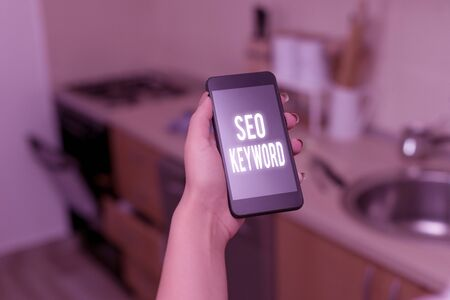 Conceptual hand writing showing Seo Keyword. Concept meaning phrases in your web content that help showing find your site woman using smartphone and technological devices inside the home