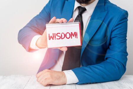Text sign showing Wisdom. Business photo showcasing the ability to use your knowledge and experience to make decisions Man holds empty paper with copy space in front of him Copy Space Stockfoto