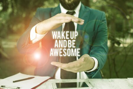 Conceptual hand writing showing Wake Up And Be Awesome. Concept meaning Rise up and Shine Start the day Right and Bright Man in front of table. Mobile phone and notes on the table Reklamní fotografie