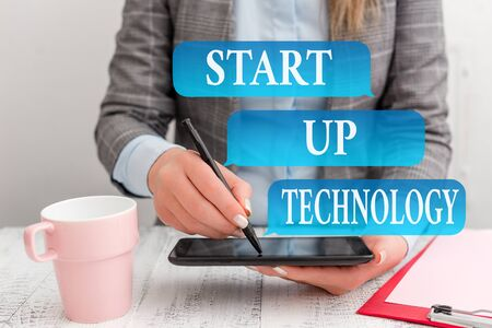 Writing note showing Start Up Technology. Business concept for Young Technical Company initially Funded or Financed Business concept with mobile phone in the hand 스톡 콘텐츠