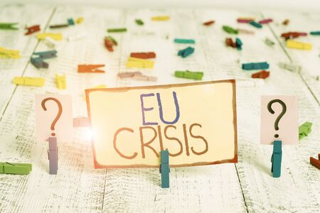 Word writing text Eu Crisis. Business photo showcasing eurozone state unable to repay or refinance their government debt Scribbled and crumbling sheet with paper clips placed on the wooden table