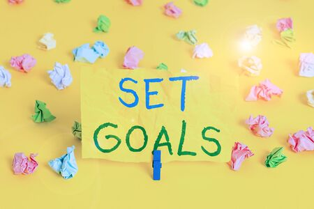 Handwriting text writing Set Goals. Conceptual photo Defining or achieving something in the future based on plan Colored crumpled papers empty reminder white floor background clothespin