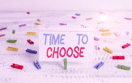 Handwriting text writing Time To Choose. Conceptual photo Judging the merits of multiple options and selecting one Green clothespin white wood background colored paper reminder office supply
