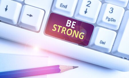 Conceptual hand writing showing Be Strong. Concept meaning able to withstand great circumstances or pressure in life White pc keyboard with note paper above the white background
