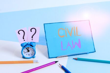 Writing note showing Civil Law. Business concept for Law concerned with private relations between members of community Mini size alarm clock beside stationary on pastel backdrop Stock Photo