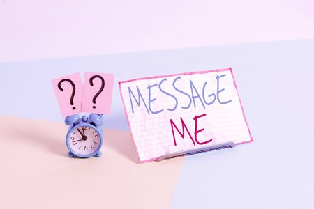 Handwriting text Message Me. Conceptual photo To ask someone to send you a short text from one mobile device Mini size alarm clock beside a Paper sheet placed tilted on pastel backdrop