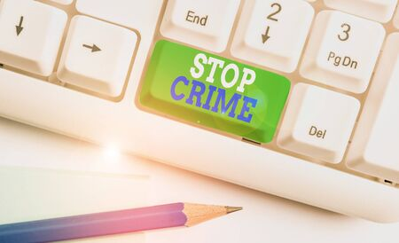 Text sign showing Stop Crime. Business photo text the effort or attempt to reduce and deter crime and criminals White pc keyboard with empty note paper above white background key copy space