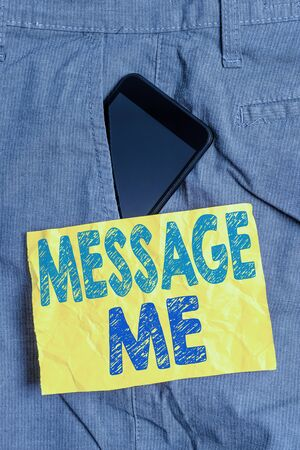 Writing note showing Message Me. Business concept for To ask someone to send you a short text from one mobile device Smartphone device inside trousers front pocket note paper Stock Photo